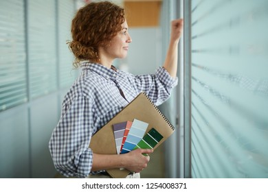 Smiling content confident beautiful design student holding sketchpad and color palettes and knocking on window while peeking through blinds in corridor