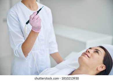 Smiling contented adult Caucasian female patient with dark hair looking upward during the electrosurgical procedure