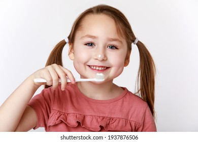 Smiling contented little girl while brushing teeth