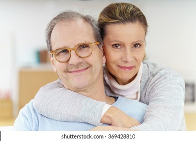 Smiling contented middle-aged man wearing glasses being hugged from behind  by his wife as 30908d9f33be