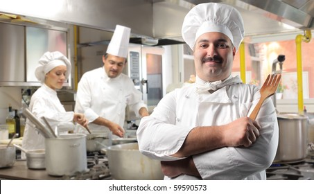 Smiling cook with two other cooks on the background