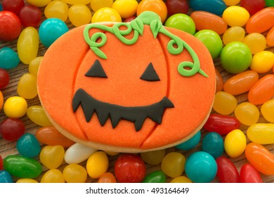 Smiling cookie pumpkin on many candy colors