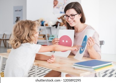 Smiling counselor holding pictures during meeting with young patient with autism