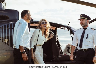 Smiling couple alight from a private helicopter with pilot standing by. Laughing man and woman disembarking the helicopter.