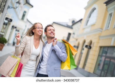 Smiling couple with bags outdoors