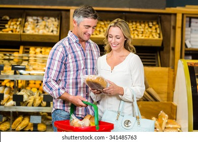 Smiling couple buying bread in supermarket