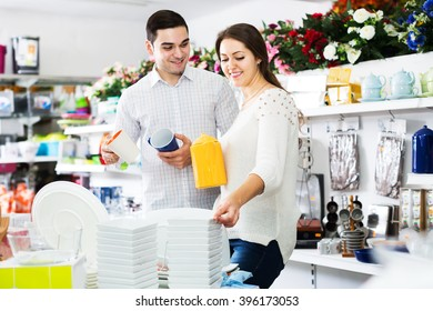 Smiling couple buying ceramic tableware in shop cookware