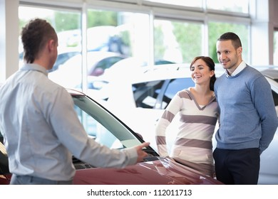 Smiling couple in a car shop with a car dealer