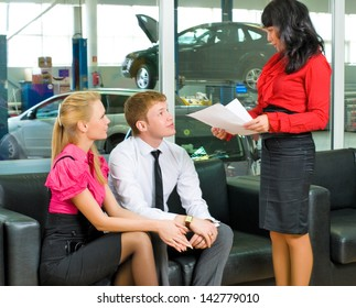 Smiling couple in car shop talking with manager