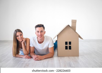 Smiling couple with cardboard house