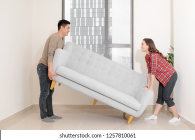 Smiling couple carrying modern chair together placing furniture moving into new home, young family discussing house improvement interior design while furnishing living room, remodeling and renovation