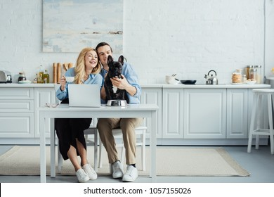 Smiling couple with coffee sitting by table with laptop in kitchen and stroking Frenchie dog