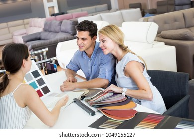 smiling couple are consulting with seller about the colors of furniture in furniture store