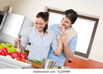 Smiling couple cook in modern kitchen with vegetables