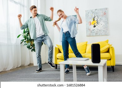 Smiling couple dancing near wireless speaker and laptop on coffee table in living room