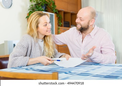 Smiling couple discussing details of marriage settlement at home