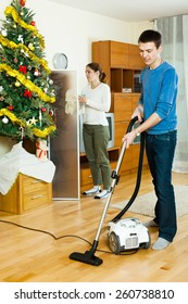 Smiling couple doing housework together in Christmas time at home