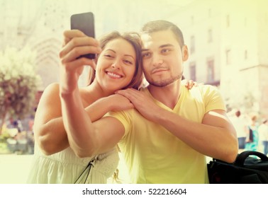 Smiling couple doing selfie during city tour at vacation