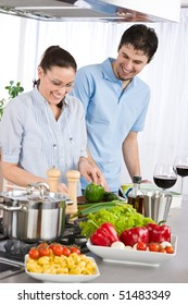 Smiling couple drink red wine cooking in kitchen with vegetables