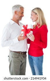 Smiling couple embracing and holding gift on white background