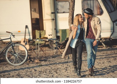 smiling couple embracing, looking at each other and walking near campervan