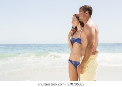 Smiling couple embracing on the beach on a sunny day