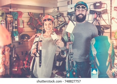 Smiling couple examining climbing equipment items in sports equipment store