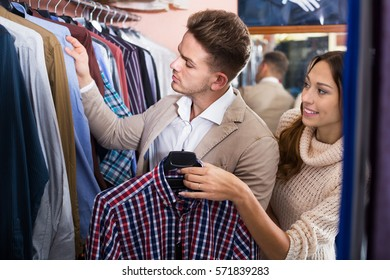 Smiling couple examining various shirts in menâ??s clothes store