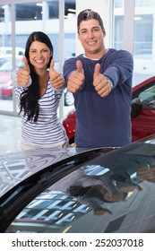 Smiling couple giving thumbs up at new car showroom