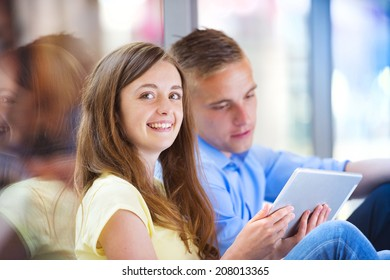 Smiling couple having fun with digital tablet in shopping mall