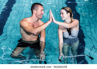 Smiling couple high fiving while cycling in the pool