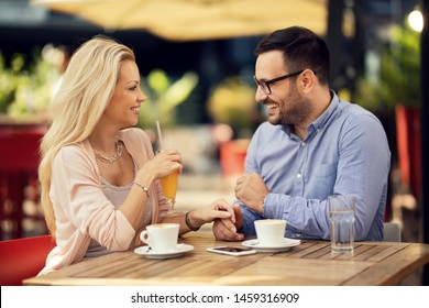 Smiling couple holding hands and talking to each other while having a date in a cafe.