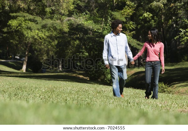 Smiling couple holding hands walking and talking in park.