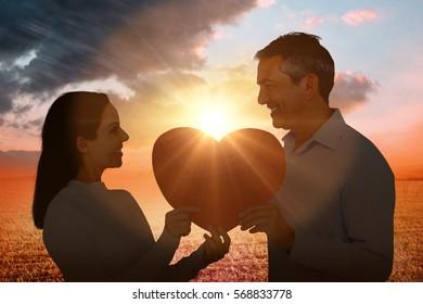 Smiling couple holding heart shape paper against sunrise over field