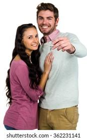 Smiling couple holding keys on white background