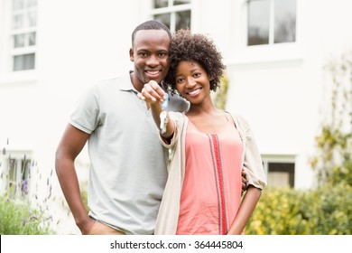 Smiling couple holding keys to their house