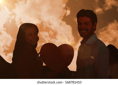 Smiling couple holding paper heart against cloudy sky