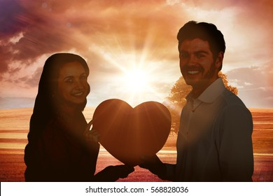 Smiling couple holding paper heart against sunrise over field with tree