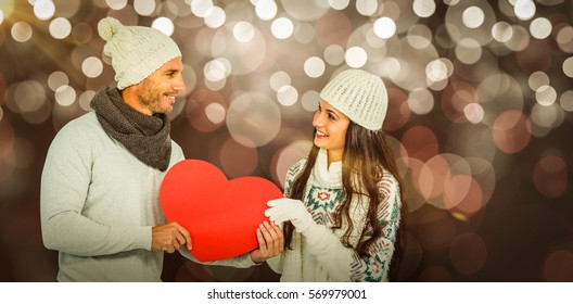 Smiling couple holding paper heart against glowing background
