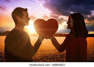 Smiling couple holding red heart shape against countryside scene