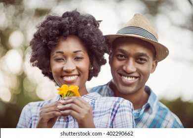 Smiling couple holding yellow flowers in the garden