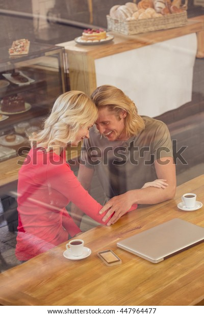 Smiling couple hugging in the cafe