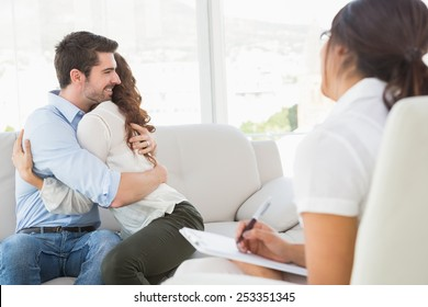 Smiling couple hugging in front of their therapist in the office