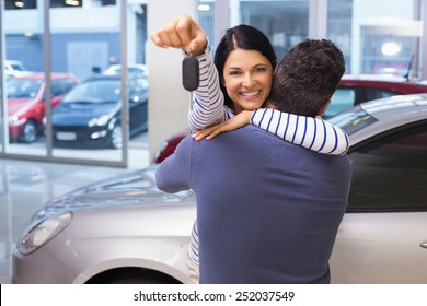 Smiling couple hugging and holding their new key at new car showroom