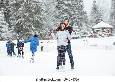 Smiling couple in ice skates hugging outdoors with snow on background