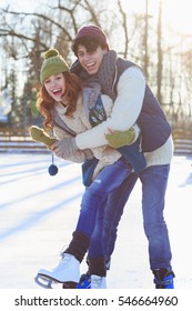 Smiling couple in ice skates hugging outdoors with snow on background. Winter sport and leisure concept. Love and fun in wintertime