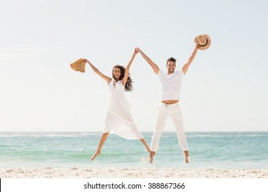 Smiling couple jumping together on the beach