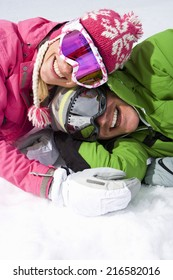 Smiling couple laying in snow together
