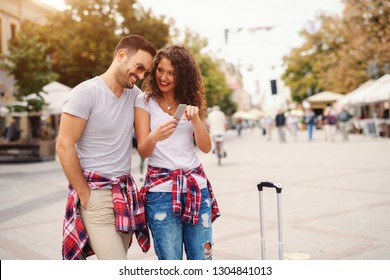 Smiling couple looking at photos on smart phone while standing on the street. Traveling concept.