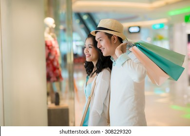 Smiling couple looking at the showcase in the shopping mall